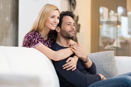 soñando: pareja de jóvenes reflexivo sonriendo mientras se relaja en el sofá en la sala de estar.