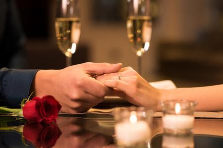 Detailní záběr na pár rukou na restauraci stůl s dvěma sklenicemi šampaňského v pozadí.
