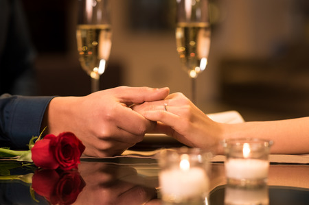 romantico: Detalle de la pareja manos en la mesa de restaurante con dos copas de champán en el fondo.