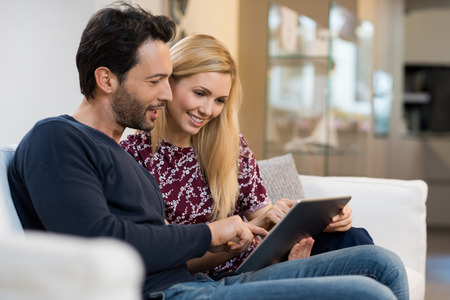 viewing: Young happy couple surfing on the web at home. Stock Photo