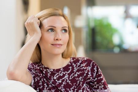 mujer pensativa: Mujer rubia joven que se inclina su cabeza contra su mano mientras se está sentado en un sofá blanco y que mira lejos. Foto de archivo