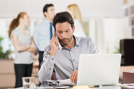 Businessman talking over phone while checking documents.