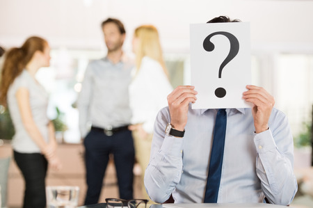 confused face: Businessman holding a question mark sign in front of his face.