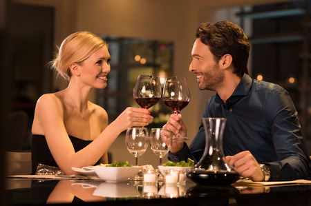 Couple toasting wine glasses during a romantic dinner in a gourmet restaurant.