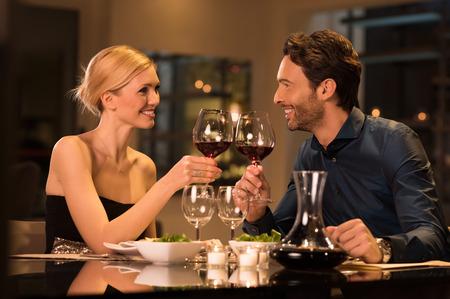 parejas: Pareja tostado copas de vino durante una cena romántica en un restaurante gourmet.