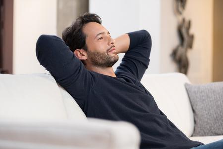 Pohledný mladý muž s rukama za hlavou sedí na gauči v obývacím pokoji.