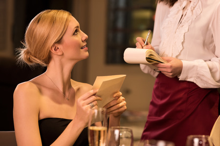 ordering: Young woman ordering food in a luxury restaurant.
