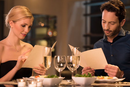 orders: Young couple reading menu and choosing meal. Stock Photo