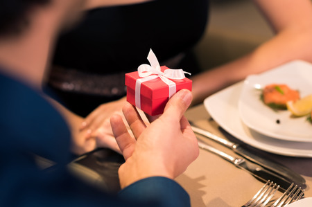 Young man gifting a small red box to young woman.