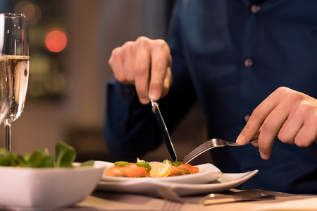 Close up of a male hands cutting and eating delicious salad with knife and fork at restaurant 免版税图像