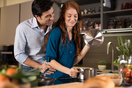 Man and woman at home preparing healthy food.