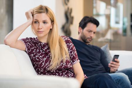 pareja enojada: Mujer joven que consigue aburrido mientras que el hombre que usa el teléfono en el fondo. Foto de archivo