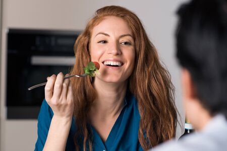 eating salad: Happy young woman eating salad with fork.