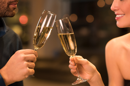 Couple toasting champagne glasses in a luxury restaurant.