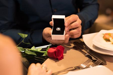 hombre joven que presenta el anillo de compromiso a la novia. Foto de archivo