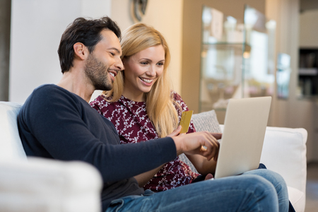 paying bills online: Portrait of happy couple paying bills online using laptop and credit card. Stock Photo
