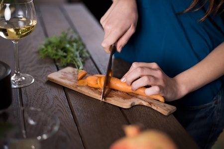 chopping: Close up of a young woman cutting carrots in kitchen. Stock Photo