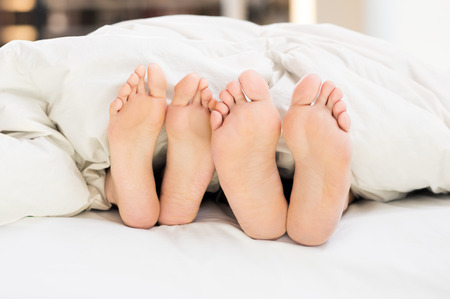 sex on bed: Close up of feet in a bed under white blanket. Stock Photo