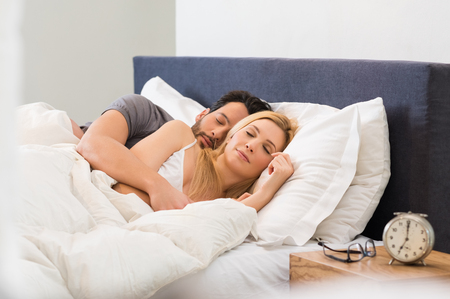 bedroom bed: Young adult couple sleeping peacefully on the bed in bedroom.