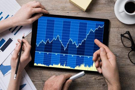 Homme d'affaires et les mains d'affaires indiquent le graphique de la tablette numérique.
