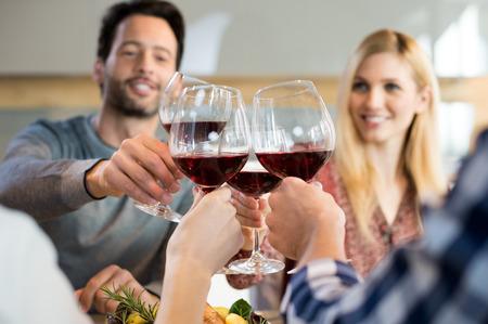 ダイニング テーブルに座って赤ワインで応援する人たちをクローズ アップ。 写真素材