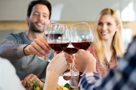 Close up of people cheering with red wine while sitting at dining table.