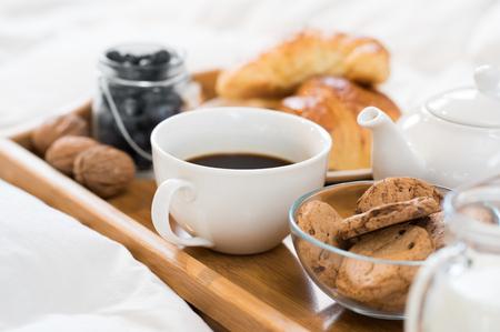 Close-up van een kopje thee met koekjes op houten dienblad in bed.