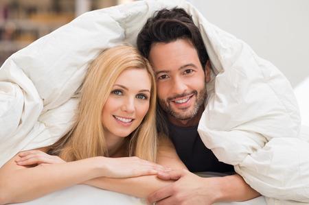 donna innamorata: Carino coppia romantica sotto un letto copre nel letto.