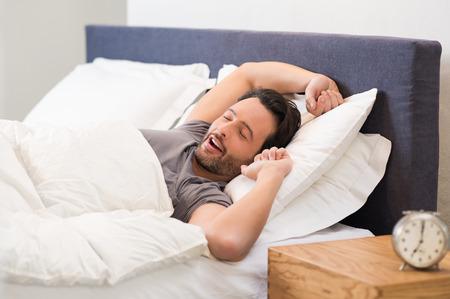 despertarse: Hombre joven que estira mientras que despertarse por la mañana.