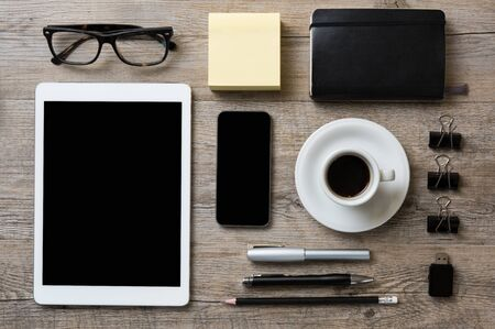 desk tidy: Top view of office desk with digital tablet, smart phone, supplies and coffe cup in wooden background. Businessman tidy desk with tablet and smartphone in black screen.