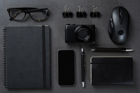 work table: Top view of glasses, mouse, pen, pencil, smartphone, notebook, and camera on a black background. Stock Photo