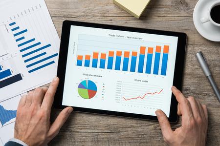 Pohled shora na digitální tablet s přehledem finančního roku na obrazovce. Reklamní fotografie