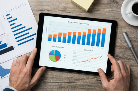 Top view of digital tablet with financial year overview on screen. Stock Photo