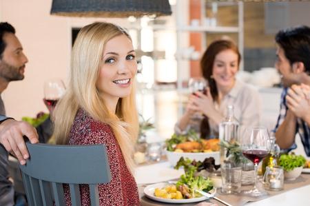 Ritratto di donna guardando la fotocamera sorridente durante un pranzo con i suoi amici.