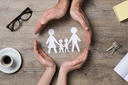proteccion: Cerca de las manos femeninas y masculinas que protegen una familia de cadena de papel.