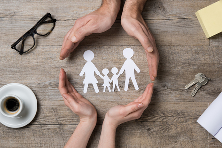 protect family: Close up of female and male hands protecting a paper chain family. Stock Photo