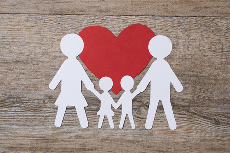 red paper: Top view of white paper chain family on red shape heart. Stock Photo