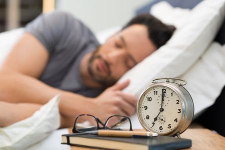 Hombre durmiendo con un reloj de alarma en primer plano. Foto de archivo