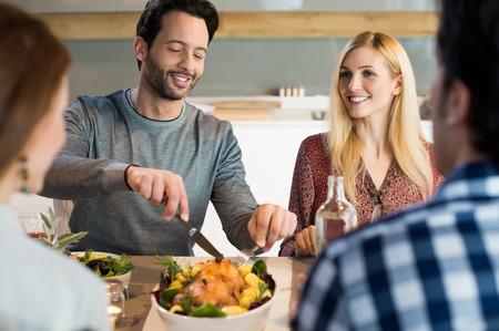 pareja comiendo: Retrato de un hombre feliz de tomar su parte de la comida. Amigos que tienen la cena o el almuerzo en casa.