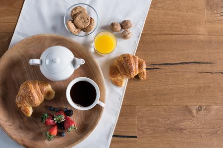 Healthy breakfast with brioche, orange juice, chocolate cookies, berries, tea and walnuts with copy space.
