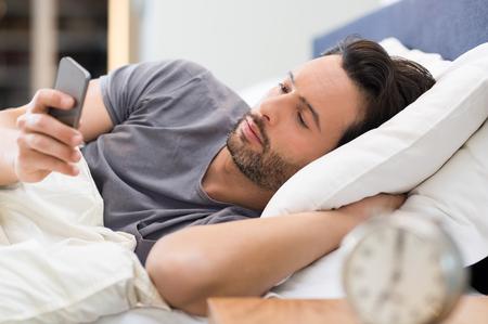 levantandose: Hombre joven que controla el teléfono al levantarse por la mañana. Foto de archivo