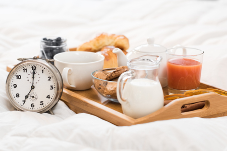 Healthy breakfast served on a tray on bed with alarm clock.
