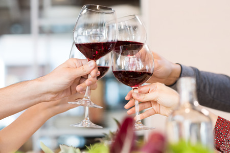 toasting: Closeup of friends toasting glasses of red wine in a party. Stock Photo