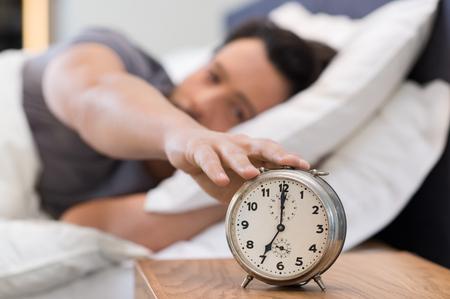 despertarse: Feliz despertar de un hombre acostado en la cama y detener el reloj de alarma. Hombre durmiendo el despertador.