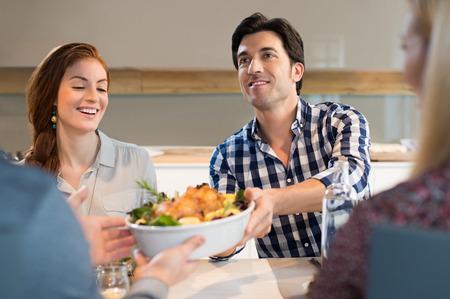 hombres jovenes: El hombre que pasa el plato de comida con el pollo asado a su amigo.
