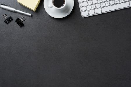 Vista de ángulo alto de la oficina de mesa negro con copia espacio. Tabla con el teclado, el ordenador, la taza y suministros de café. Foto de archivo - 53544765
