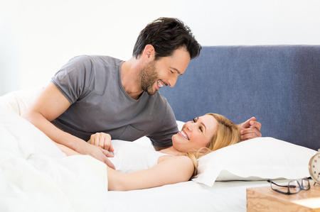 Young couple looking at each other and embracing while lying in bed.