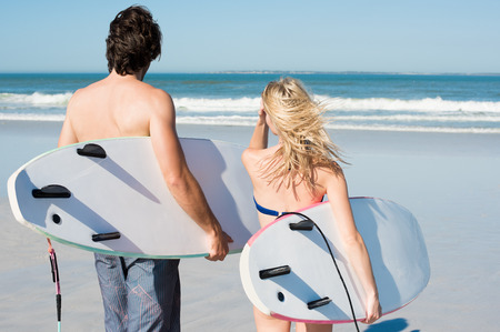 bikini couple: Surfers ready to swim in the sea. Portrait of couple holding surfboard under their arms. Rear view of couple with surfboards walking at the beach. Stock Photo
