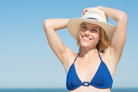 person woman: Girl wearing blue bikini and straw hat looking at camera. Blonde woman wearing sun hat standing at the beach. Young woman relaxing and smiling on beach with sky like a copy space. Stock Photo