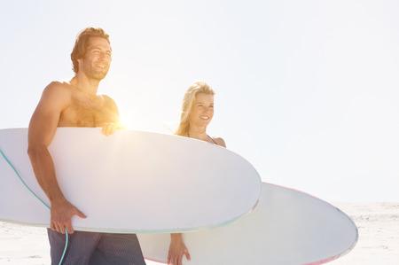 ビーチでサーフボードと若いサーファーのカップル。海岸線でサーフボードの上に立って幸せ笑顔の友人。幸せなカップルがビーチでサーフィンし